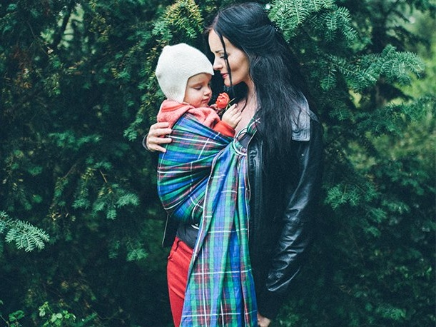 Woman carries her little girl in a tartan ring sling baby carrier