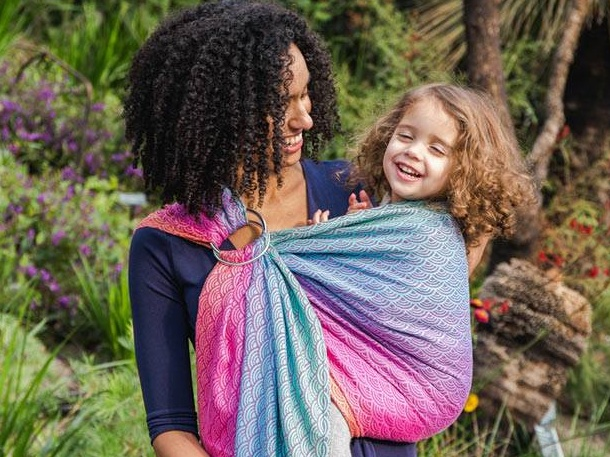 Woman carries her toddler in a brightly coloured ring sling baby carrier