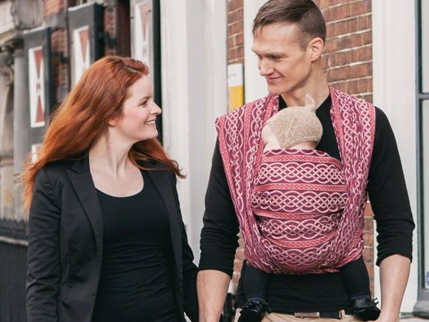 Couple walking, man carries their child in a Oscha Slings woven wrap with a celtic knot pattern