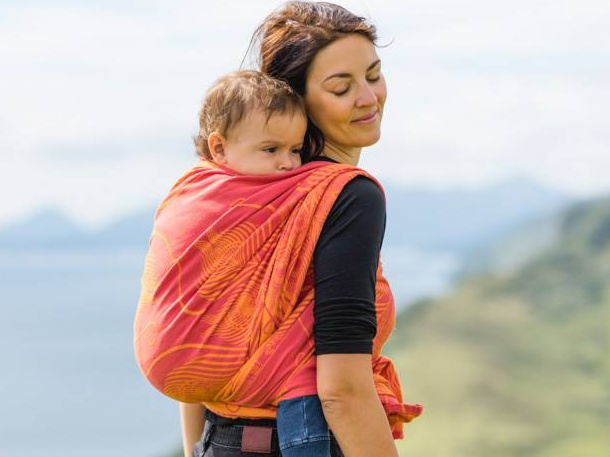 Woman carrying baby on her back using a bright organge baby wrap.
