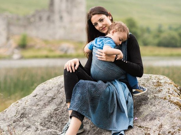 Woman carries her child in a blue woven wrap in the Scottish highlands